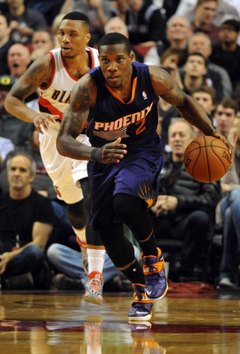Apr 4, 2014; Portland, OR, USA; Phoenix Suns guard Eric Bledsoe (2) brings the ball up the court as Portland Trail Blazers guard Damian Lillard (0) trails during the fourth quarter of the game against the Phoenix Suns at Moda Center. the Suns won the game 109-93. Mandatory Credit: Steve Dykes-USA TODAY Sports