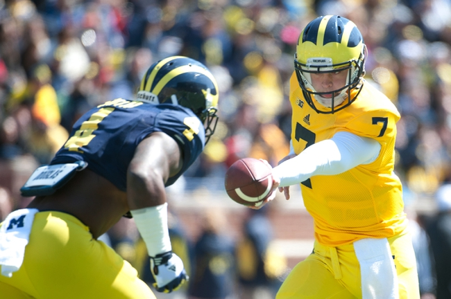 Apr 5, 2014; Ann Arbor, MI, USA; Michigan Wolverines quarterback Shane Morris (7) hands off to running back De'Veon Smith (4) before the Spring Game at Michigan Stadium. Mandatory Credit: Tim Fuller-USA TODAY Sports