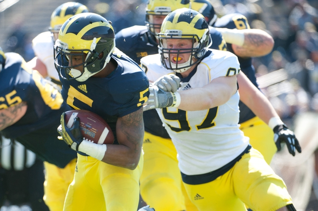 Apr 5, 2014; Ann Arbor, MI, USA; Michigan Wolverines running back Justice Hayes (5) runs with the ball in front of linebacker Brennen Beyer (97) during the Spring Game at Michigan Stadium. Mandatory Credit: Tim Fuller-USA TODAY Sports