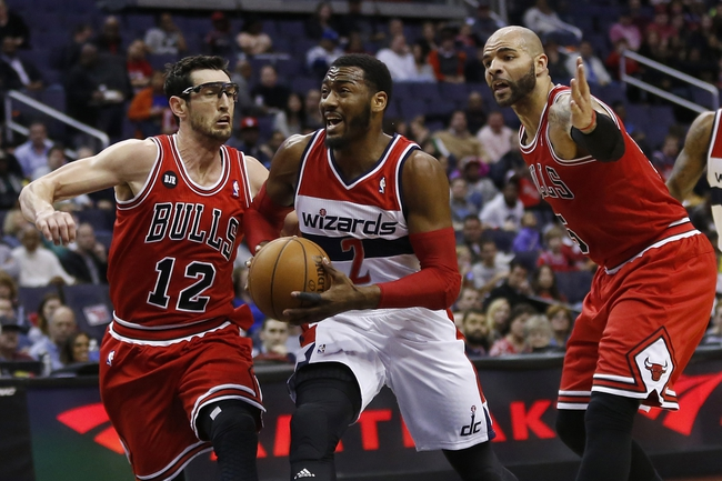 Apr 5, 2014; Washington, DC, USA; Washington Wizards guard John Wall (2) dribbles the ball as Chicago Bulls guard Kirk Hinrich (12) and Bulls forward Carlos Boozer (5) defend in the first quarter at Verizon Center. Mandatory Credit: Geoff Burke-USA TODAY Sports