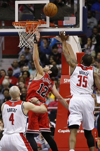 Apr 5, 2014; Washington, DC, USA; Chicago Bulls guard Kirk Hinrich (12) shoots the ball a Washington Wizards forward Trevor Booker (35) defends in the first quarter at Verizon Center. Mandatory Credit: Geoff Burke-USA TODAY Sports