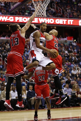 Apr 5, 2014; Washington, DC, USA; Washington Wizards forward Trevor Ariza (1) attempts to shoot the ball as Chicago Bulls center Joakim Noah (13) and Bulls forward Carlos Boozer (5) defend in the second quarter at Verizon Center. Mandatory Credit: Geoff Burke-USA TODAY Sports
