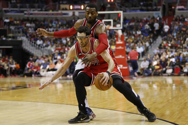 Apr 5, 2014; Washington, DC, USA; Chicago Bulls guard Kirk Hinrich (12) dribbles the ball as Washington Wizards guard John Wall (2) defends in the fourth quarter at Verizon Center. The Bulls won 96-78. Mandatory Credit: Geoff Burke-USA TODAY Sports