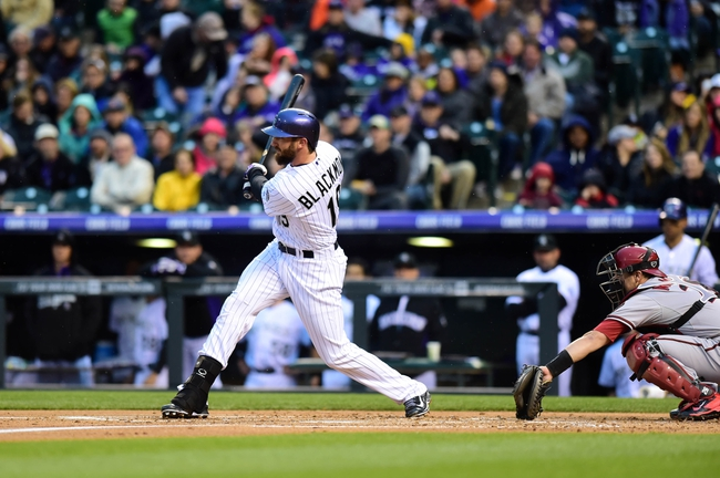 Apr 5, 2014; Denver, CO, USA; Colorado Rockies right fielder Charlie Blackmon (19) singles in the first inning against the Arizona Diamondbacks at Coors Field. Mandatory Credit: Ron Chenoy-USA TODAY Sports