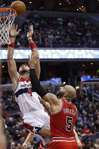 Apr 5, 2014; Washington, DC, USA; Washington Wizards center Marcin Gortat (4) shoots the ball over Chicago Bulls forward Carlos Boozer (5) in the second quarter at Verizon Center. Mandatory Credit: Geoff Burke-USA TODAY Sports