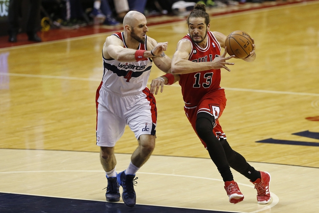 Apr 5, 2014; Washington, DC, USA; Chicago Bulls center Joakim Noah (13) dribbles the ball as Washington Wizards center Marcin Gortat (4) defends in the third quarter at Verizon Center. The Bulls won 96-78. Mandatory Credit: Geoff Burke-USA TODAY Sports