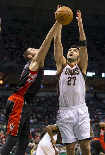 Apr 5, 2014; Milwaukee, WI, USA; Toronto Raptors center Jonas Valanciunas (17) and Milwaukee Bucks center Zaza Pachulia (27) battle for a rebound during the third quarter at BMO Harris Bradley Center. Mandatory Credit: Jeff Hanisch-USA TODAY Sports