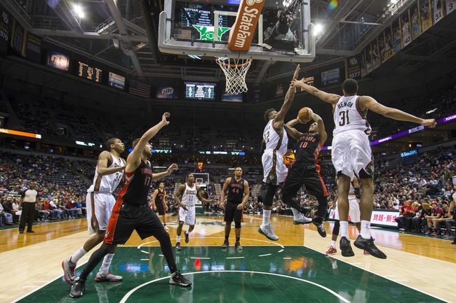 Apr 5, 2014; Milwaukee, WI, USA; Toronto Raptors guard DeMar DeRozan (10) shoots the ball between Milwaukee Bucks forward Jeff Adrien (12) and center John Henson (31) during the third quarter at BMO Harris Bradley Center. Mandatory Credit: Jeff Hanisch-USA TODAY Sports