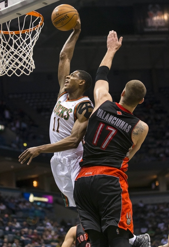 Apr 5, 2014; Milwaukee, WI, USA; Milwaukee Bucks guard Brandon Knight (11) dunks the ball as Toronto Raptors center Jonas Valanciunas (17) defends during the third quarter at BMO Harris Bradley Center. Mandatory Credit: Jeff Hanisch-USA TODAY Sports