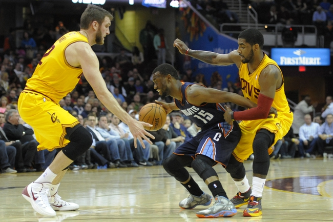 Apr 5, 2014; Cleveland, OH, USA; Charlotte Bobcats guard Kemba Walker (15) dribbles between Cleveland Cavaliers center Spencer Hawes (32) and guard Kyrie Irving (2) in the first quarter at Quicken Loans Arena. Mandatory Credit: David Richard-USA TODAY Sports