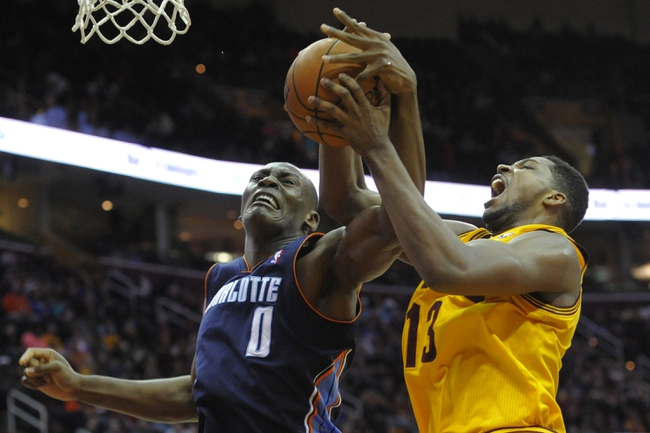Apr 5, 2014; Cleveland, OH, USA; Charlotte Bobcats center Bismack Biyombo (0) battles for a rebound with Cleveland Cavaliers forward Tristan Thompson (13) in the fourth quarter at Quicken Loans Arena. Mandatory Credit: David Richard-USA TODAY Sports