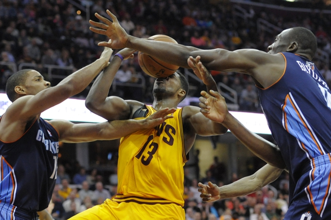 Apr 5, 2014; Cleveland, OH, USA; Cleveland Cavaliers forward Tristan Thompson (13) battles for a rebound with Charlotte Bobcats guard Gary Neal (L) and center Bismack Biyombo (0) in the fourth quarter at Quicken Loans Arena. Mandatory Credit: David Richard-USA TODAY Sports
