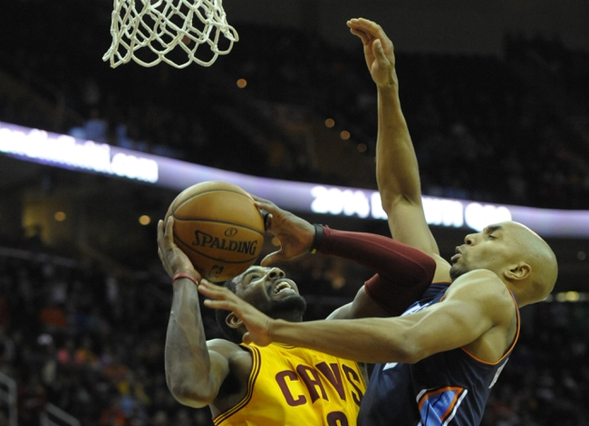 Apr 5, 2014; Cleveland, OH, USA; Cleveland Cavaliers guard Kyrie Irving (L) shoots the ball as Charlotte Bobcats guard Gerald Henderson (9) defends in overtime at Quicken Loans Arena. Mandatory Credit: David Richard-USA TODAY Sports