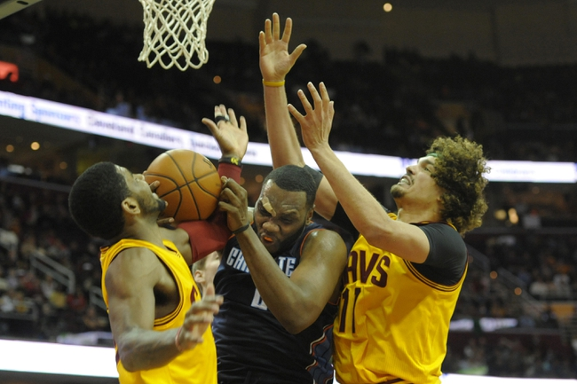 Apr 5, 2014; Cleveland, OH, USA; Charlotte Bobcats center Al Jefferson (25) battles for a rebound with Cleveland Cavaliers guard Kyrie Irving (L) and center Anderson Varejao (17) in the fourth quarter at Quicken Loans Arena. Mandatory Credit: David Richard-USA TODAY Sports
