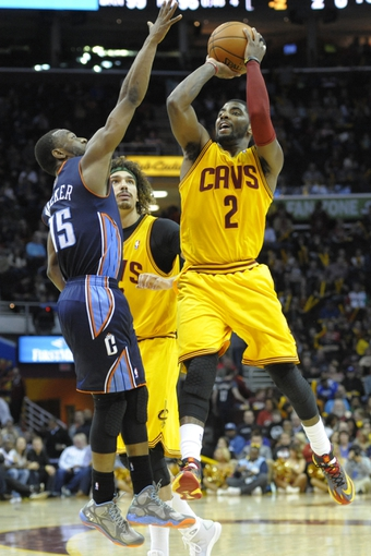 Apr 5, 2014; Cleveland, OH, USA; Cleveland Cavaliers guard Kyrie Irving (2) shoots the ball over Charlotte Bobcats guard Kemba Walker (15) in overtime at Quicken Loans Arena. Mandatory Credit: David Richard-USA TODAY Sports