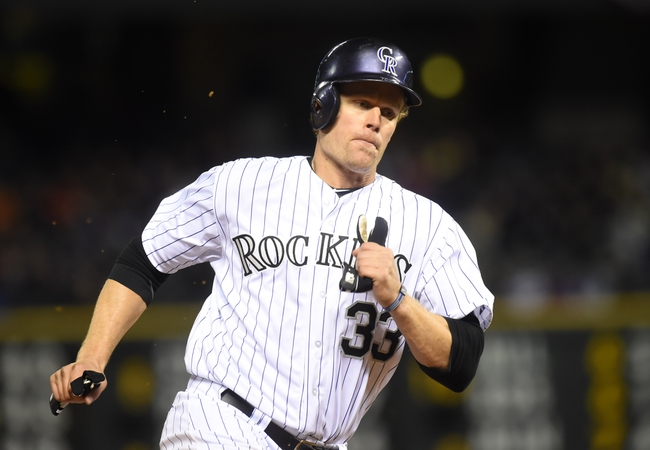 Apr 5, 2014; Denver, CO, USA; Colorado Rockies first baseman Justin Morneau (33) heads for home in the eight inning against the Arizona Diamondbacks at Coors Field. The Rockies defeated the Diamondbacks 9-4. Mandatory Credit: Ron Chenoy-USA TODAY Sports