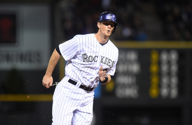 Apr 5, 2014; Denver, CO, USA; Colorado Rockies second baseman DJ LeMahieu (9) heads home to score in the fifth inning against the Arizona Diamondbacks at Coors Field. The Rockies defeated the Diamondbacks 9-4. Mandatory Credit: Ron Chenoy-USA TODAY Sports