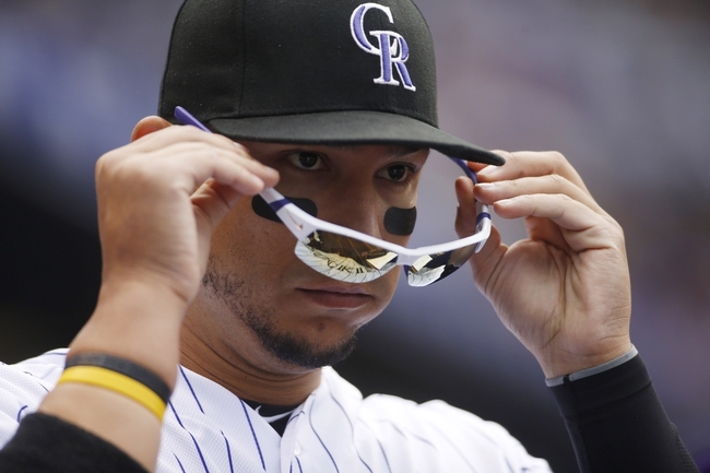 Apr 6, 2014; Denver, CO, USA; Colorado Rockies left fielder Carlos Gonzalez (5) during the second inning against the Arizona Diamondbacks at Coors Field. Mandatory Credit: Chris Humphreys-USA TODAY Sports