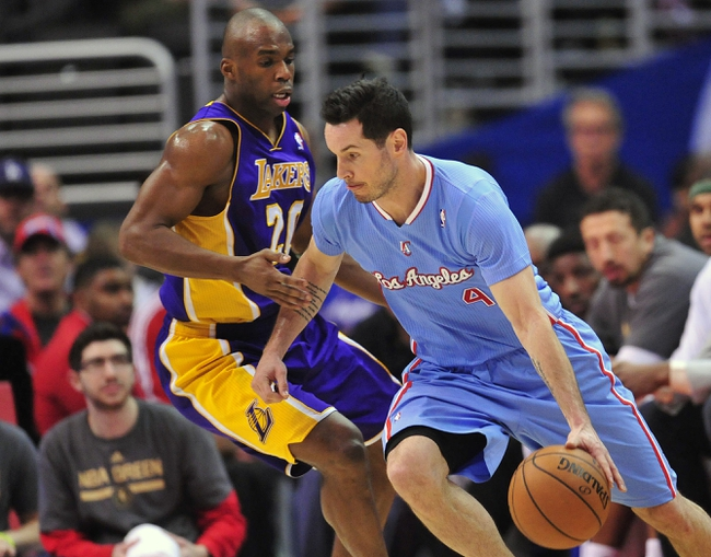 April 6, 2014; Los Angeles, CA, USA; Los Angeles Clippers guard J.J. Redick (4) moves the ball against Los Angeles Lakers guard Jodie Meeks (20) during the first half at Staples Center. Mandatory Credit: Gary A. Vasquez-USA TODAY Sports