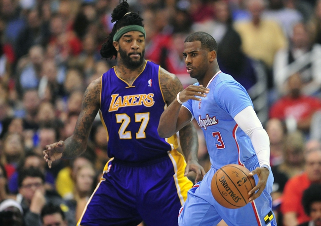 April 6, 2014; Los Angeles, CA, USA; Los Angeles Clippers guard Chris Paul (3) controls the ball against Los Angeles Lakers forward Jordan Hill (27) during the first half at Staples Center. Mandatory Credit: Gary A. Vasquez-USA TODAY Sports