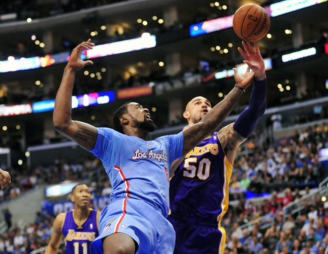 April 6, 2014; Los Angeles, CA, USA; Los Angeles Clippers center DeAndre Jordan (6) goes for a rebound  against Los Angeles Lakers center Robert Sacre (50) during the first half at Staples Center. Mandatory Credit: Gary A. Vasquez-USA TODAY Sports