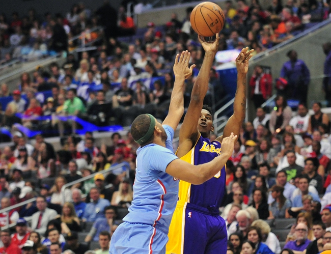 April 6, 2014; Los Angeles, CA, USA; Los Angeles Lakers forward Nick Young (0) shoots a three point basket against the Los Angeles Clippers during the first half at Staples Center. Mandatory Credit: Gary A. Vasquez-USA TODAY Sports