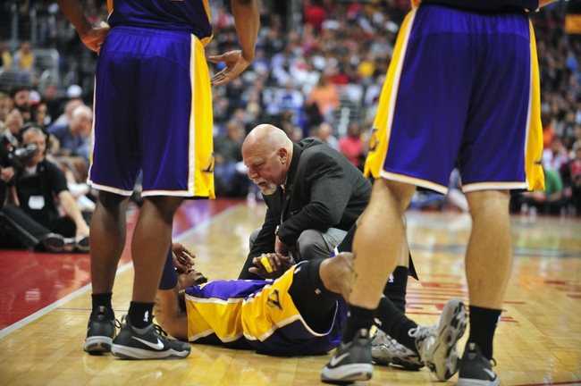 April 6, 2014; Los Angeles, CA, USA; Los Angeles Lakers trainer Gary Vitti looks at guard Kent Bazemore (6) after suffering an apparent injury in the first half at Staples Center. Mandatory Credit: Gary A. Vasquez-USA TODAY Sports