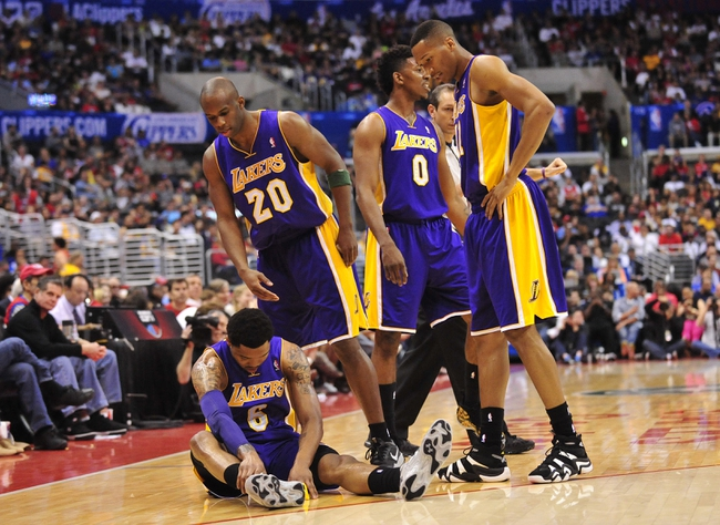 April 6, 2014; Los Angeles, CA, USA; Los Angeles Lakers guard Kent Bazemore (6) suffers an apparent injury as guard Jodie Meeks (20), forward Nick Young (0) and forward Wesley Johnson (11) help him during a stoppage in play in the first half at Staples Center. Mandatory Credit: Gary A. Vasquez-USA TODAY Sports