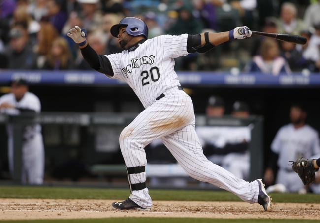 Apr 6, 2014; Denver, CO, USA; Colorado Rockies catcher Wilin Rosario (20) hits a double during the fifth inning against the Colorado Rockies at Coors Field. Mandatory Credit: Chris Humphreys-USA TODAY Sports