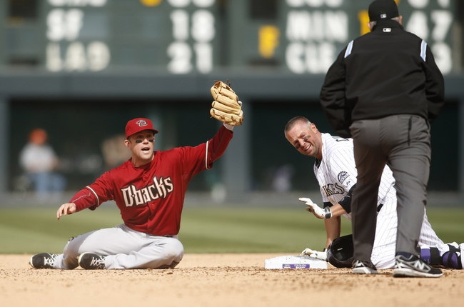 Apr 6, 2014; Denver, CO, USA; Arizona Diamondbacks shortstop Chris Owings (left) contests a call by second base umpire Mike Muchlinski (right) after Colorado Rockies first baseman Michael Cuddyer (3) was ruled safe sliding into second base for a double during the fourth inning at Coors Field. Mandatory Credit: Chris Humphreys-USA TODAY Sports
