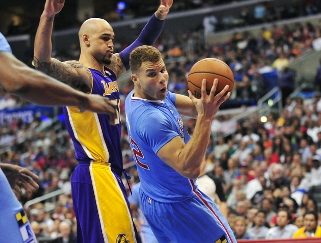 April 6, 2014; Los Angeles, CA, USA; Los Angeles Clippers forward Blake Griffin (32) loses his balance while controlling the ball against Los Angeles Lakers center Robert Sacre (50) during the second half at Staples Center. Mandatory Credit: Gary A. Vasquez-USA TODAY Sports