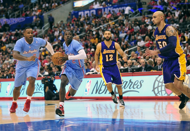 April 6, 2014; Los Angeles, CA, USA; Los Angeles Clippers guard Darren Collison (2) moves to the basket against Los Angeles Lakers center Robert Sacre (50) and guard Kendall Marshall (12)  during the second half at Staples Center. Mandatory Credit: Gary A. Vasquez-USA TODAY Sports