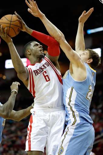 Apr 6, 2014; Houston, TX, USA; Houston Rockets forward Terrence Jones (6) shoots the ball against Denver Nuggets center Timofey Mozgov (25) during the second quarter at Toyota Center. Mandatory Credit: Andrew Richardson-USA TODAY Sports