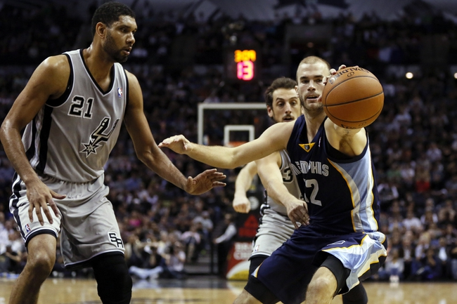Apr 6, 2014; San Antonio, TX, USA; Memphis Grizzlies guard Nick Calathes (12) reaches for a loose ball in front of San Antonio Spurs forward Marco Belinelli (3) during the second half at AT&T Center. Mandatory Credit: Soobum Im-USA TODAY Sports