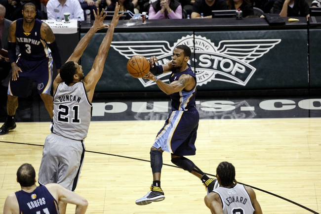 Apr 6, 2014; San Antonio, TX, USA; Memphis Grizzlies guard Mike Conley (right) passes the ball as San Antonio Spurs forward Tim Duncan (21) defends during the second half at AT&T Center. The Spurs won 112-92. Mandatory Credit: Soobum Im-USA TODAY Sports