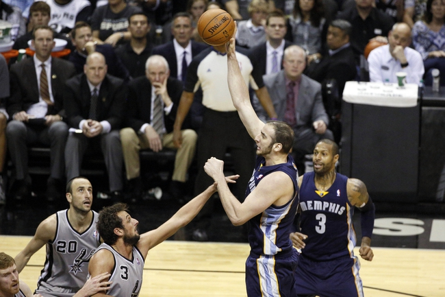 Apr 6, 2014; San Antonio, TX, USA; Memphis Grizzlies center Kosta Koufos (top) shoots the ball over San Antonio Spurs forward Marco Belinelli (3) during the second half at AT&T Center. The Spurs won 112-92. Mandatory Credit: Soobum Im-USA TODAY Sports
