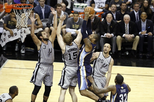 Apr 6, 2014; San Antonio, TX, USA; Memphis Grizzlies forward James Johnson (3) shoots the ball as San Antonio Spurs forward Marco Belinelli (3) and Matt Bonner (15) defend during the second half at AT&T Center. The Spurs won 112-92. Mandatory Credit: Soobum Im-USA TODAY Sports