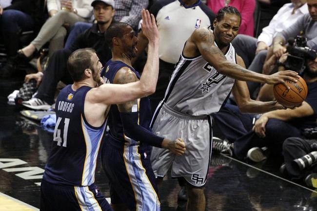 Apr 6, 2014; San Antonio, TX, USA; San Antonio Spurs forward Kawhi Leonard (right) looks to pass as Memphis Grizzlies forward James Johnson (center) and Kosta Koufos (left) defend during the second half at AT&T Center. The Spurs won 112-92. Mandatory Credit: Soobum Im-USA TODAY Sports