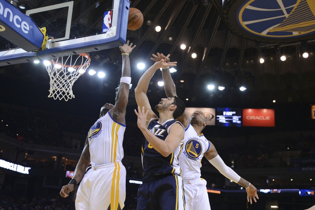 Apr 6, 2014; Oakland, CA, USA; Utah Jazz center Enes Kanter (0, center) shoots the ball against Golden State Warriors center Jermaine O'Neal (7, left) and forward Marreese Speights (5) during the fourth quarter at Oracle Arena. The Warriors defeated the Jazz 130-102. Mandatory Credit: Kyle Terada-USA TODAY Sports