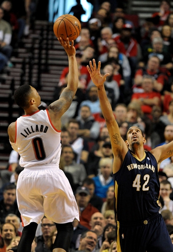 Apr 6, 2014; Portland, OR, USA; Portland Trail Blazers guard Damian Lillard (0) shoots over New Orleans Pelicans center Alexis Ajinca (42) during the first quarter at Moda Center. Mandatory Credit: Steve Dykes-USA TODAY Sports