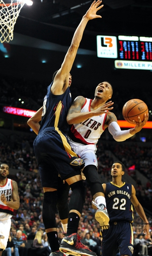 Apr 6, 2014; Portland, OR, USA; Portland Trail Blazers guard Damian Lillard (0) drives to the basket on New Orleans Pelicans forward Anthony Davis (23) during the third quarter of the game at the Moda Center. The Blazers won the game 100-94. Mandatory Credit: Steve Dykes-USA TODAY Sports