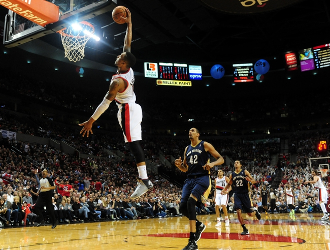 Apr 6, 2014; Portland, OR, USA; Portland Trail Blazers guard Damian Lillard (0) dunks the ball as New Orleans Pelicans center Alexis Ajinca (42) during the third quarter of the game at the Moda Center. The Blazers won the game 100-94. Mandatory Credit: Steve Dykes-USA TODAY Sports