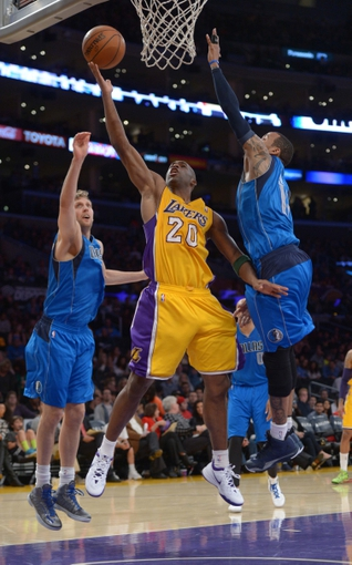 Apr 4, 2014; Los Angeles, CA, USA; Los Angeles Lakers guard Jodie Meeks (20) is defended by Dallas Mavericks forward Dirk Nowitzki (41) and guard Devin Harris (20) at Staples Center. The Mavericks defeated the Lakers 107-95.  Mandatory Credit: Kirby Lee-USA TODAY Sports