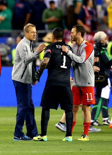 Apr 2, 2014; Glendale, AZ, USA; USA head coach Jurgen Klinsmann (left) with goalie Nick Rimando (center) and midfielder Brad Davis (11) following the game against Mexico during a friendly match at University of Phoenix Stadium. Mandatory Credit: Mark J. Rebilas-USA TODAY Sports