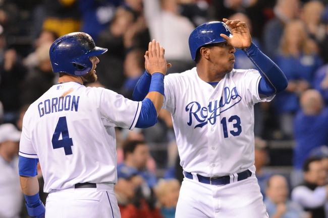 Apr 7, 2014; Kansas City, MO, USA; Kansas City Royals catcher Salvador Perez (13) is congratulated by left fielder Alex Gordon (4) after scoring in the sixth inning against the Tampa Bay Rays at Kauffman Stadium. Mandatory Credit: Denny Medley-USA TODAY Sports