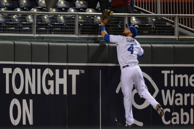 Apr 7, 2014; Kansas City, MO, USA; Kansas City Royals left fielder Alex Gordon (4) climbs the outfield wall trying for a catch in the ninth inning against the Tampa Bay Rays at Kauffman Stadium. The Royals won 4-2.  Mandatory Credit: Denny Medley-USA TODAY Sports