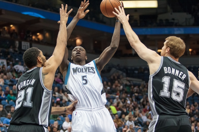 Apr 8, 2014; Minneapolis, MN, USA; Minnesota Timberwolves center Gorgui Dieng (5) shoots in the second quarter against the San Antonio Spurs forward Tim Duncan (21) at Target Center. Mandatory Credit: Brad Rempel-USA TODAY Sports