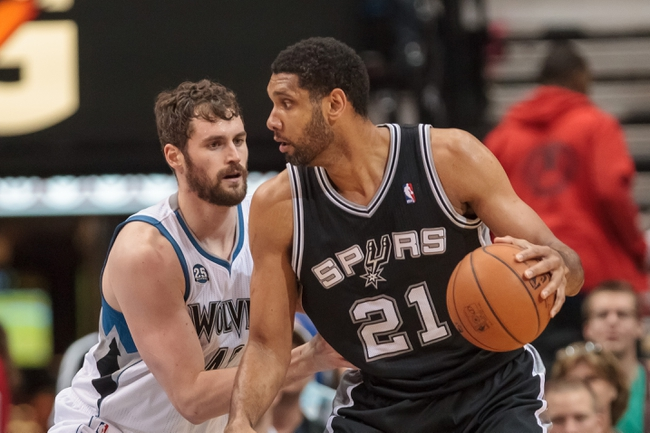 Apr 8, 2014; Minneapolis, MN, USA; San Antonio Spurs forward Tim Duncan (21) dribbles in the second quarter against the Minnesota Timberwolves forward Kevin Love (42)~ at Target Center. Mandatory Credit: Brad Rempel-USA TODAY Sports