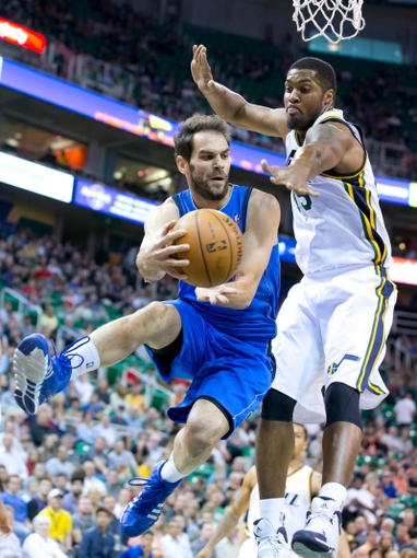 Apr 8, 2014; Salt Lake City, UT, USA; Dallas Mavericks guard Jose Calderon (8) passes from under the basket while defended by Utah Jazz center Derrick Favors (15) during the first quarter at EnergySolutions Arena. Mandatory Credit: Russ Isabella-USA TODAY Sports