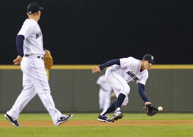 Apr 8, 2014; Seattle, WA, USA; Seattle Mariners shortstop Brad Miller (5) fields a ground ball hit by Los Angeles Angels center fielder Mike Trout (27) (not pictured) during the first inning at Safeco Field. Mandatory Credit: Steven Bisig-USA TODAY Sports